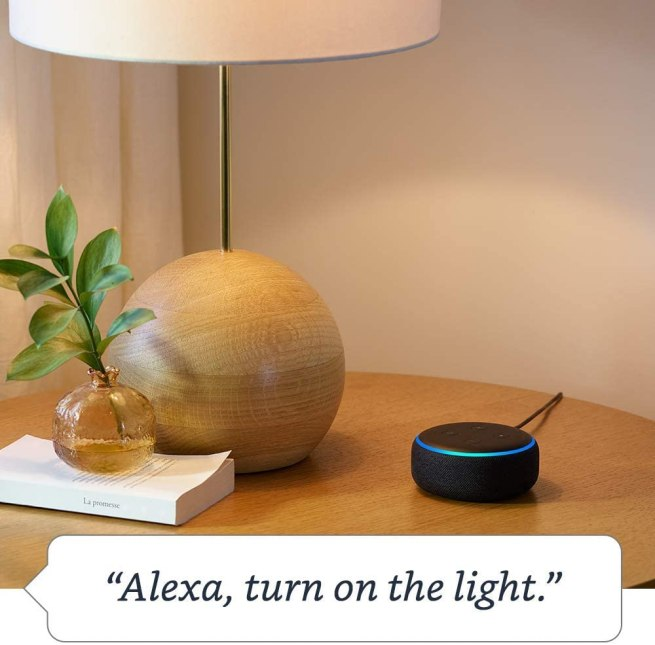 Side table with a lamp and a black Echo Dot device.