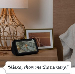 Bedside table with a lamp and a rectangular Echo Show showing a baby in a crib.