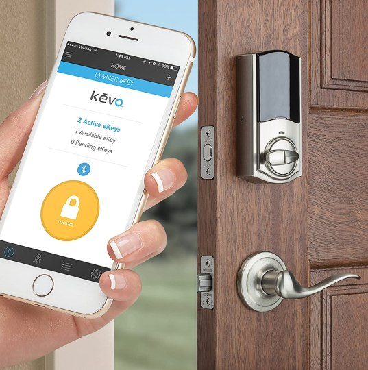 Front door with Kwikset Smart Lock in the background. A hand holding a smart phone showing the Kevo app in the foreground.